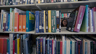 Image of two students through stacks of library books.