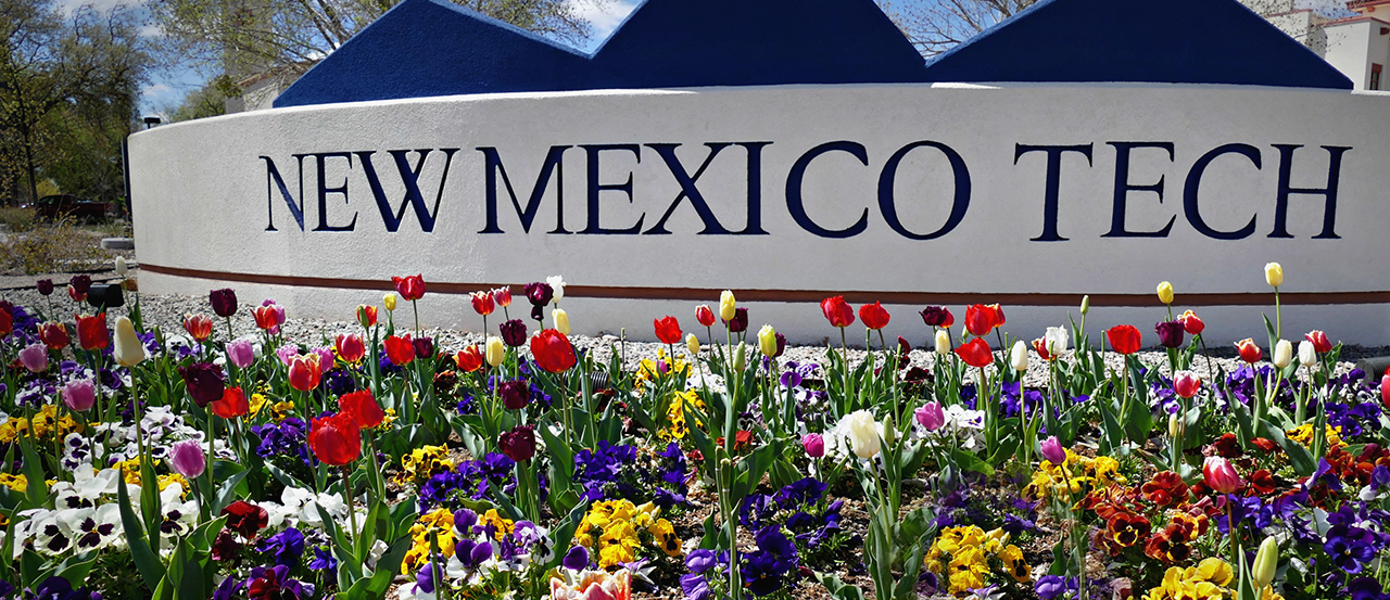 Image of the New Mexico Tech entry sign surrounded by blooming flowers