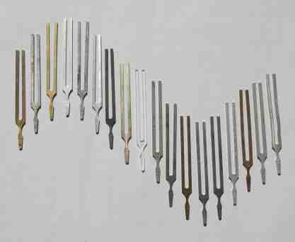 18 tuning forks lying on a table in a sine wave pattern