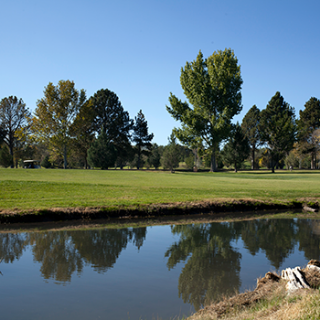 Image of the NMT golf course, with a lake in the foreground