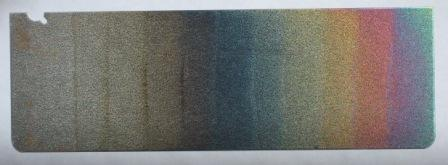 Steel sheet showing a variety of colors, each representing a stage in how it is anodized.