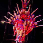 Image of many Chinese acrobats on a bicycle.